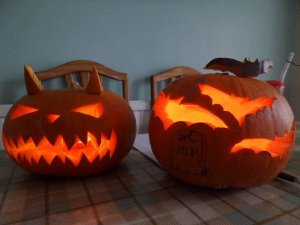Two pumpkins were laid out on a family competition night. One with standard jack face and horns, the other had bats carved with a head stone drawn on.